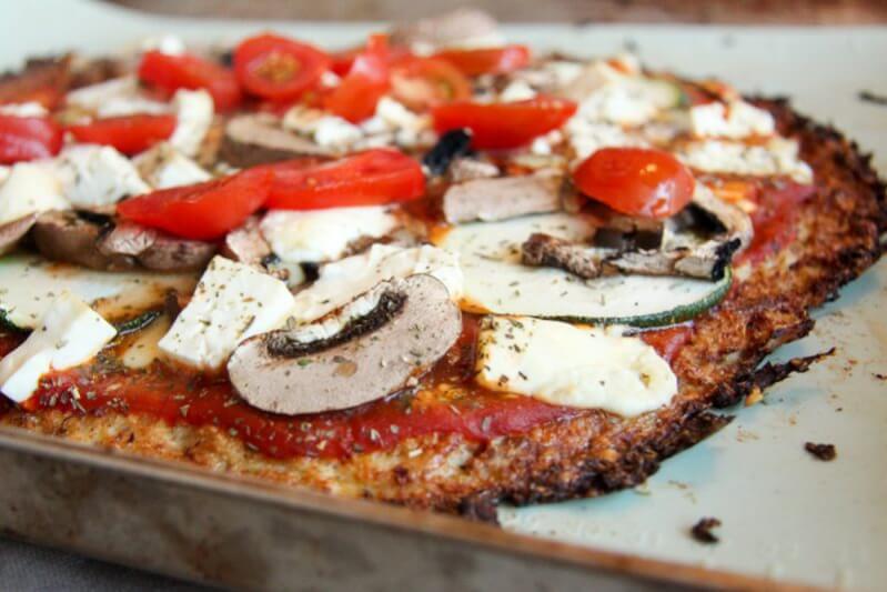 Knuspriger Blumenkohl Pizzateig belegt mit Champignons, Zucchini, Feta und Tomaten